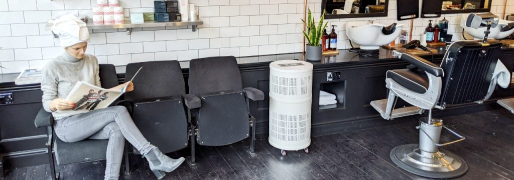 Rensair hospital-grade air purifier in a barber with person